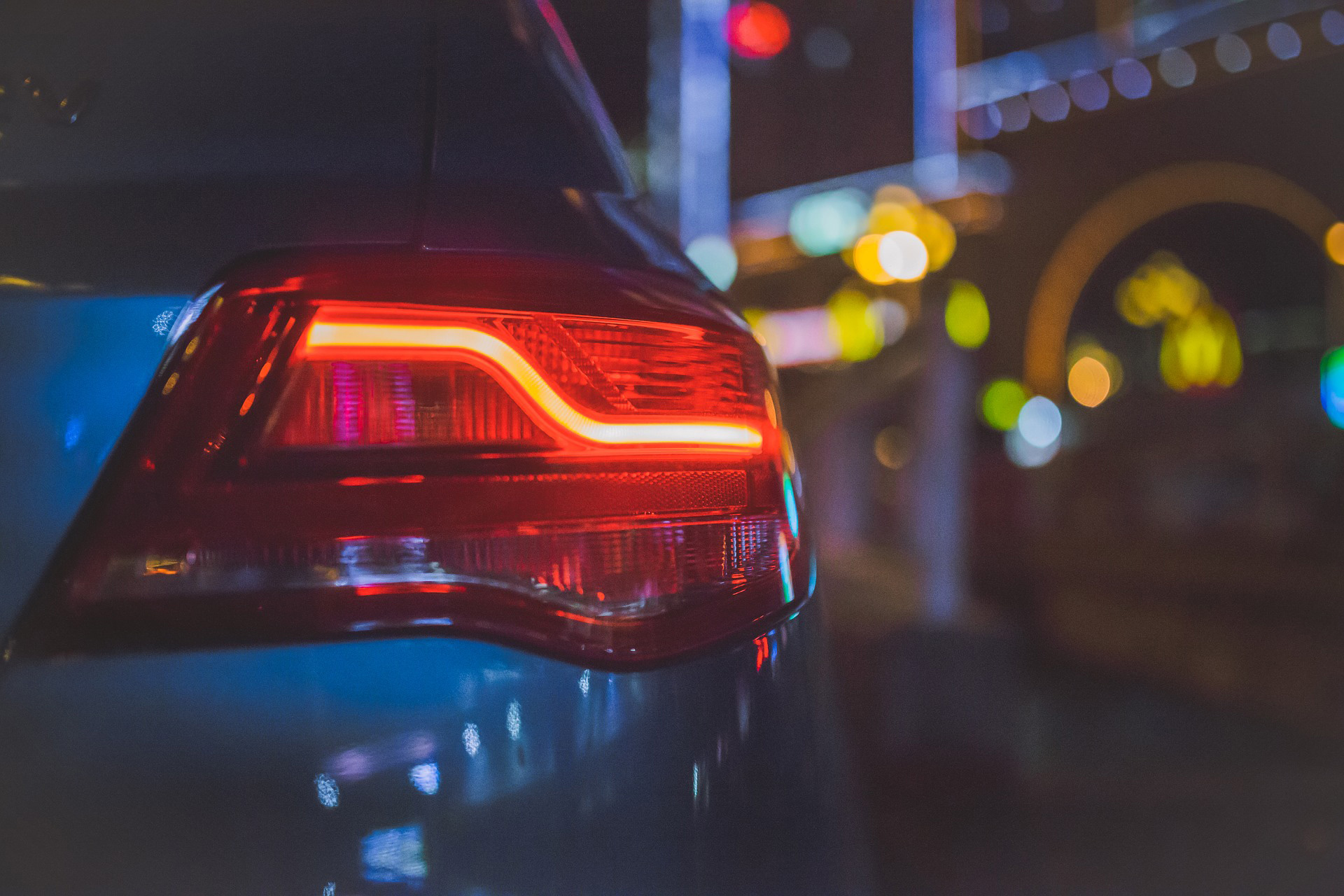 Rücklicht eines Fahrschulautos, bei Nacht.
